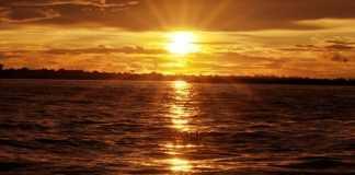 Sol beija o rio durante o pôr do sol na Amazônia