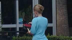 Mulher loira alta com vestido semi transparente azul