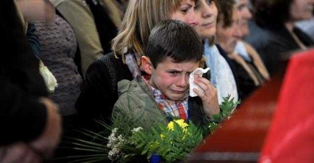 Irmão mais novo se despede de Segei durante o funeral Visitar página Visualizar imagem