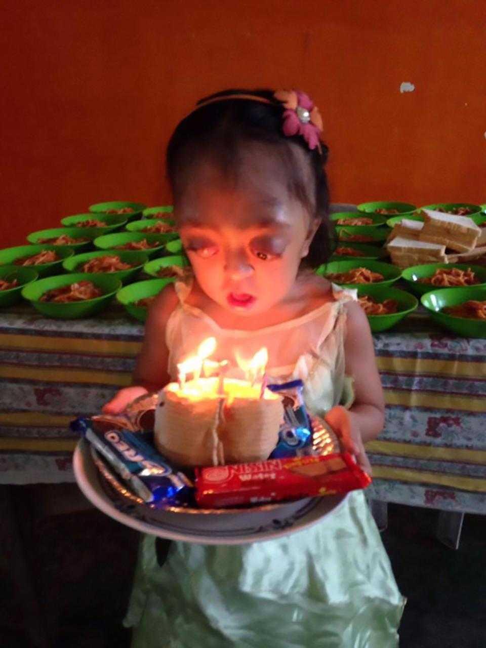 Anabelle feliz após o seu resgate milagroso, segurando um bolo de aniversários. / Foto : CENTRAL EUROPEAN NEWS