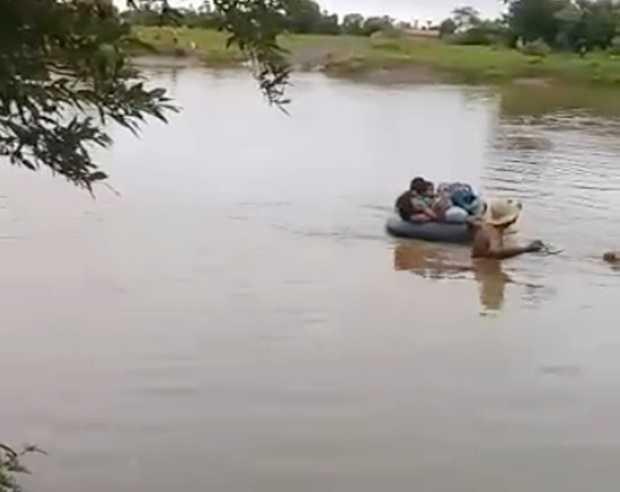 Crianças utilizam boias para atravessar rio e chegar até o ponto do ônibus escolar - Imagem: Reprodução Youtube